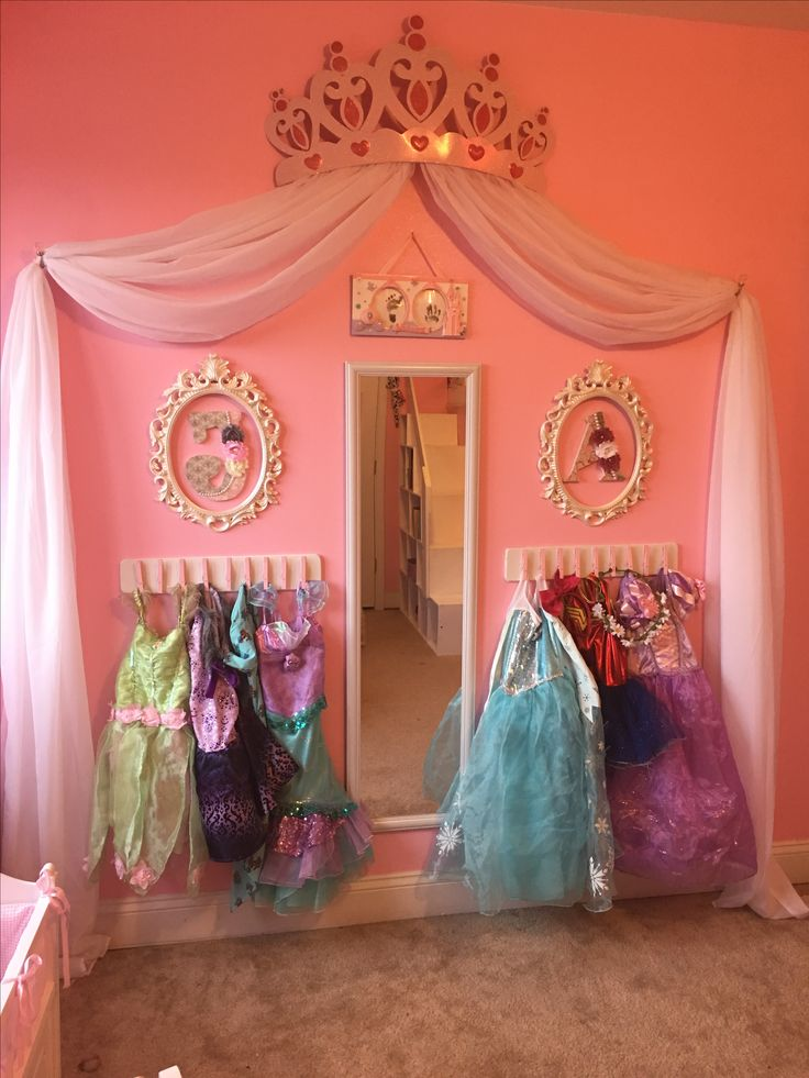 Princess dress up storage diy. Cheap and super easy! Frees space by putting the dresses on the wall. Spray painted wood boards and clothes pins, then hot glued the clothes pins to the wood board and hung on the wall. The kids can add and remove the dresses with ease!
