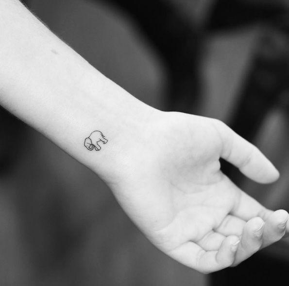 Tiny elephant tattoo by Evan