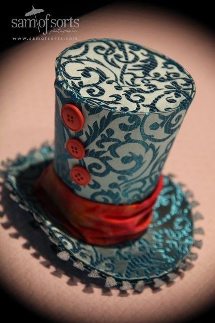 Turquoise Swirl Brocade Mini Top Hat Trimmed with Orange and Pink Buttons. $67.00, via Etsy.