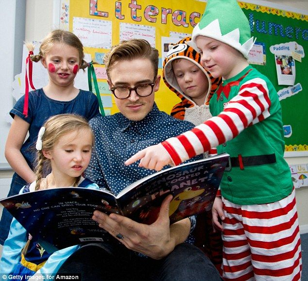 Whose the dinosaur now? Tom Fletcher reads his infectious children's book to pupils in vibrant fancy dress at Cranbourne Primary school, Winkfield on Thursday