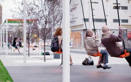 A bus stop with swings! This is in Montreal and every summer they put up a series of musical swings. If you look in the background you can see more people swinging away.    Each swing is a set of four and has its own unique sound, but if you are in perfect harmony with the other 3 seats then an actual song is played. The theory is that you communicate and interact with people more if it's for a specific goal and i