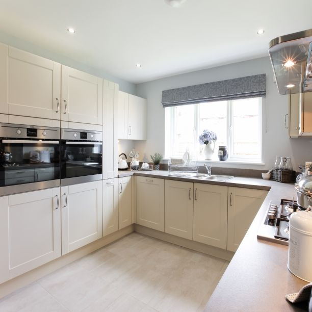 Create a kitchen that is timeless by using a neutral colour scheme. Choosing cream and light grey hues will make the room an open and airy space that will stand the test of time. #InteriorDesign #InteriorDesignIdeas #Home #FirstHome #NewHome #TaylorWimpey #Kitchen #Cream #Grey #Timeless