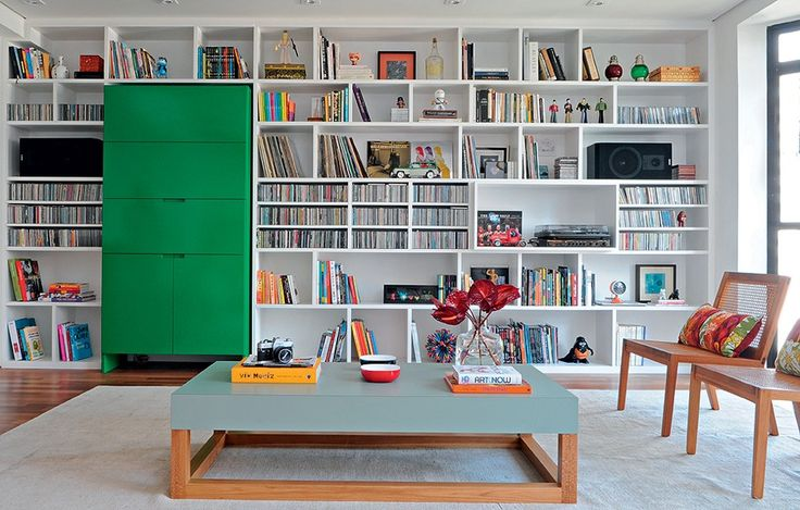 """O destaque da sala é a marcenaria, projetada pelas arquitetas Taícia e Tatiana Marques. """"Ocupamos a parede inteira para que coubesse tudo do morador"""", diz Taícia. A peça tem espaço no qual se encaixa o móvel verde, responsável por um toque de cor"""