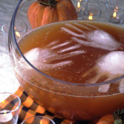 Un saladier de jus pommes-raisins avec des mains en glaçon réalisées avec des gants ménagers fins.