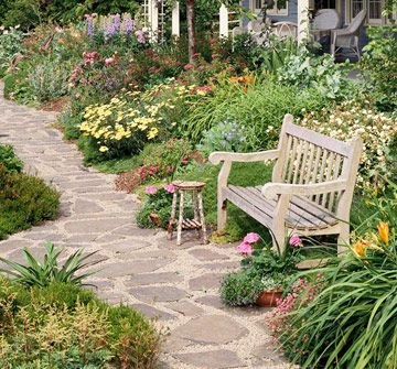 Cottage Garden Path-Create stairs in your yard to help visitors navigate a steep incline. These wood-bordered steps continue a path that meanders past two waterfalls, vine maples, and bushy evergreen plantings.