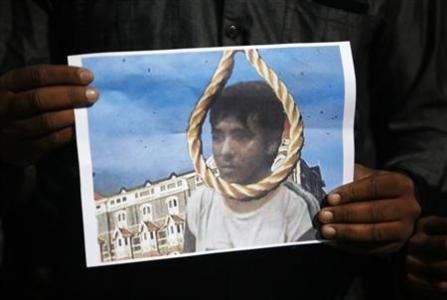 A man holds a picture of Mohammad Ajmal Kasab with a noose, as he celebrates Kasab's execution, in the western Indian city of Ahmedabad November 21, 2012. REUTERS-Amit Dave