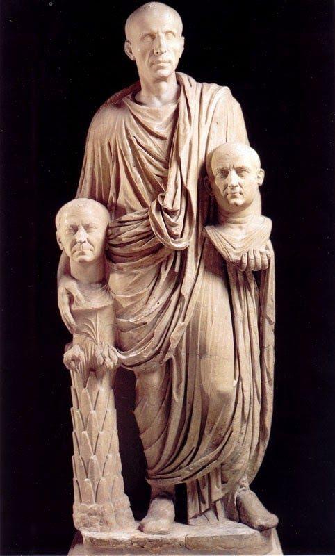 """Esta foto representa a un patricio romano quien está vestido con la toga que simboliza la ciudadanía romana. Sostiene bustos de sus ancestros. Ellos siempre tuvieron una ideología conservadora: se veían a sí  mismos como la esencia de lo romano. El nombre de Patricios le venía dado porque provenía de """"padre"""", en referencia a que eran hijos de los padres fundadores de Roma."""