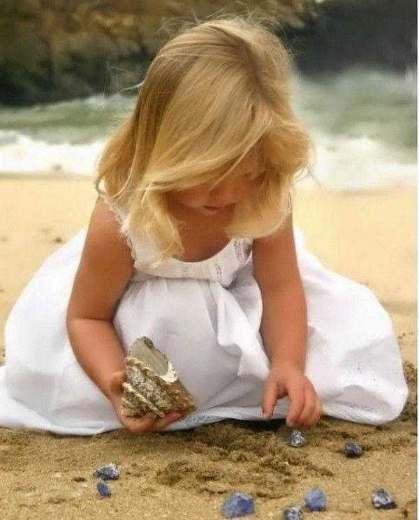 Fillette blonde en robe blanche ramassant des coquillages au bord de la mer.