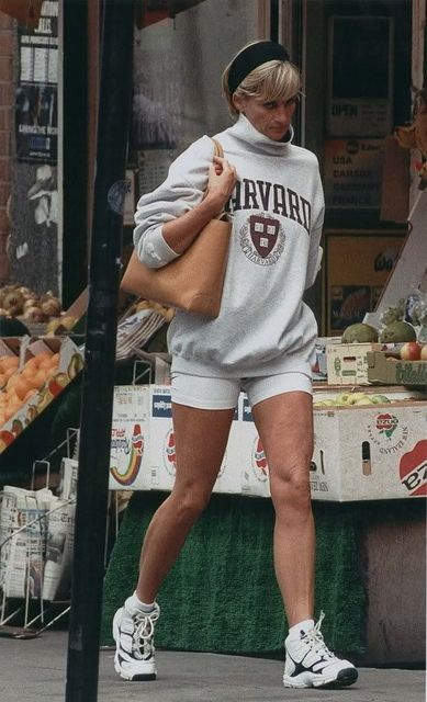 1997: Princess Diana out on a jog, but by the shops in London. Wearing an oversized white or light grey Harvard sweatshirt, white lycra shorts and a black headband, carrying a tan bag.