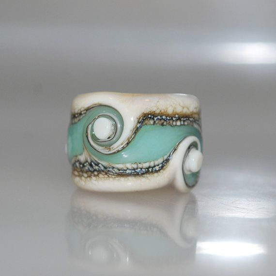 Artisan handmade glass dread bead. A cream base, striped and swirled with brown and seafoam green.  This beachy dreadlock bead has a 12mm hole and it measures approx. 19mm x 13.5mm    All of the lampwork beads in my shop were made by me in my home studio in Sydney and have been annealed in my digital kiln to remove stress and prevent cracking.    I do my best to take quality photos that show items clearly and as true to color as possible, however please understand that different computer…
