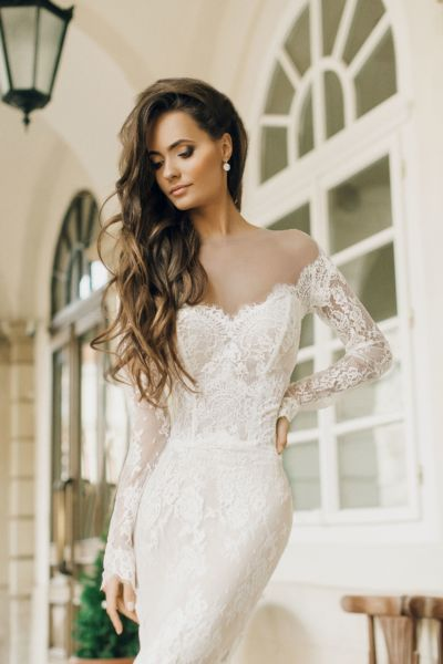 Perfect bridal couture for fashion aficionados! Tender and seductive mermaid silhouette dress with tie off-the-shoulder long sleeves transparent bodice and tie pencil skirt flared from the knees. Luxury wedding dress made of high-quality knit and totally covered by precious Shantilier lace.