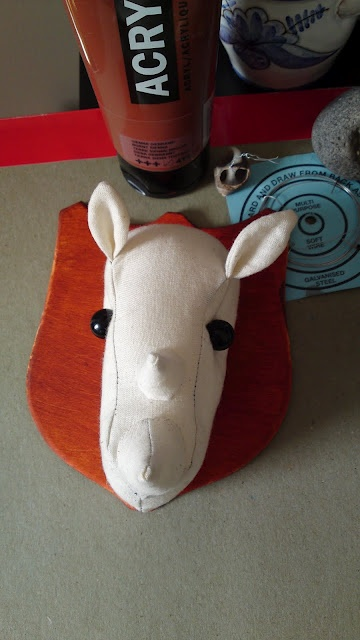 Prototype Rhino head attached to a wooden sheild...