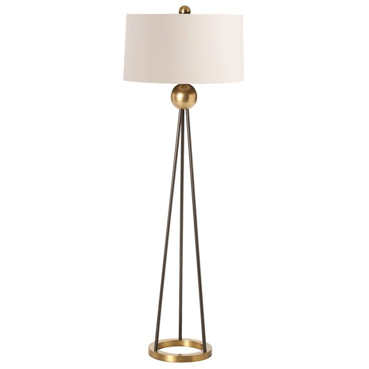 Contemporary iron floor lamp with three black rods which form a tripod from the open circle brass base and connect at the top to an antique brass finish ball accent. Topped with an ivory microfiber sh