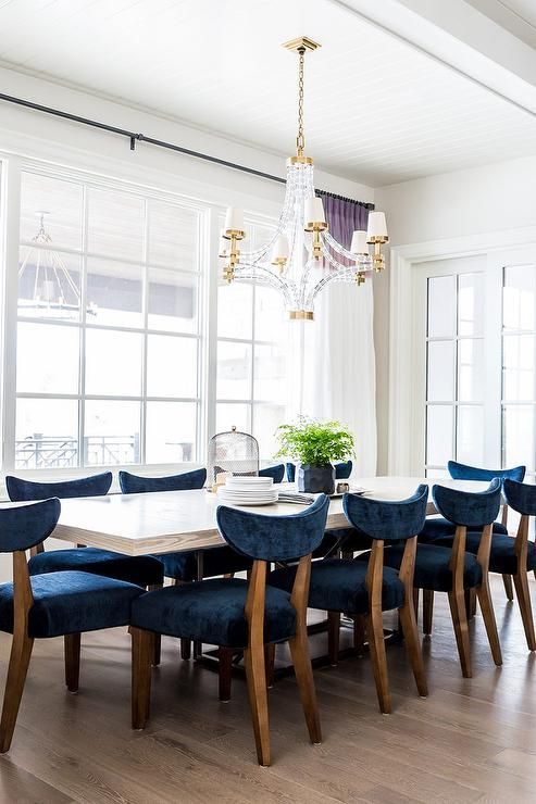 Gorgeous dining room boasts a white beadboard ceiling accented with a crystal and brass chandelier, Large Crystal Cube Chandelier, illuminating a white dining table lined with navy blue velvet dining chairs placed before windows dressed in white curtains with purple banding.