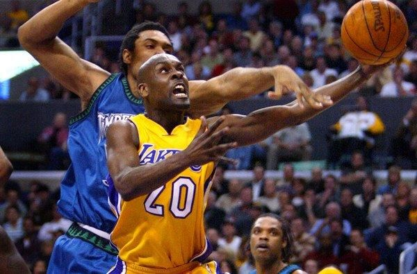 Gary Payton puts up a layup after driving past Timberwolves center Michael Olowokandi in March 2004 during Payton's only season with the Lakers.