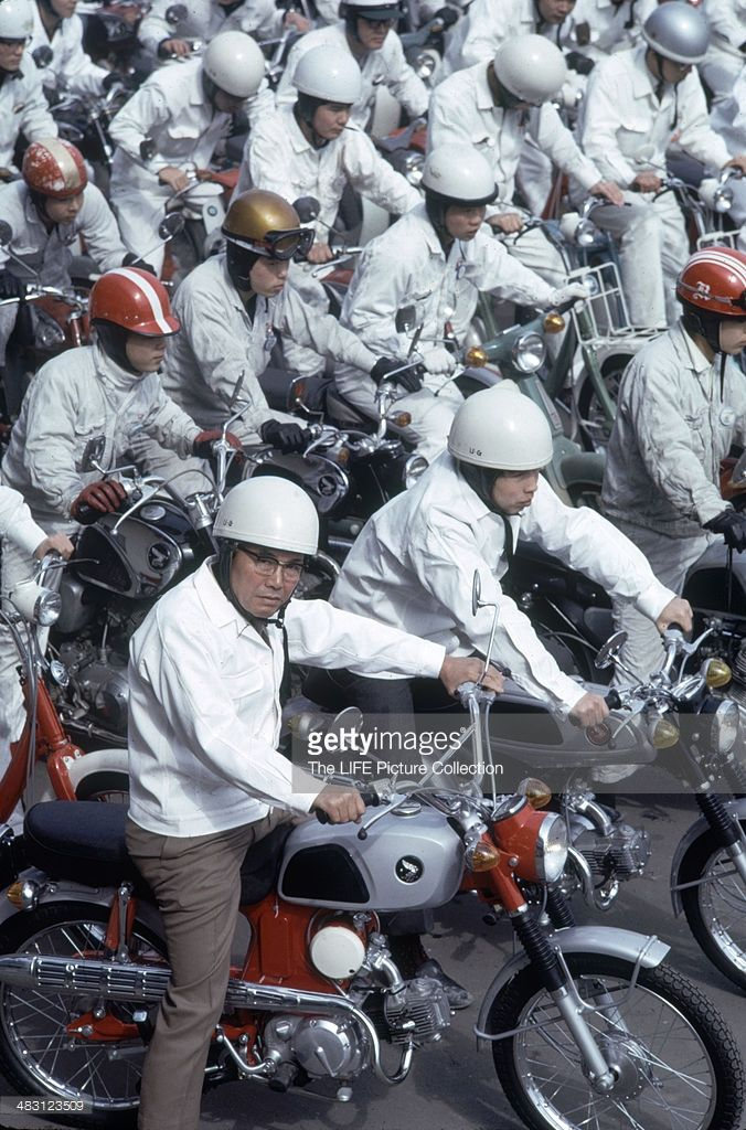 Portrait of Japanese industrialist and founder of Honda corporation Soichiro Honda (1906 - 1991) (center, fore) poses on a motorcycle among dozen of Honda employees, on a variety of scooters, motorbikes, and motorcyles, Tokyo, Japan 1967.