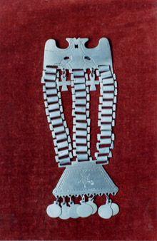 TRAPELACUCHA:  Adorno pectoral tradicionalmente utilizado por las mujeres mapuche. representa el mundo celestial y terrenal del hombre. La placa superior muestra una pareja de aves, en donde se manifiesta la dualidad entre lo femenino y masculino, sus eslabones son la conexión entre el cielo y la tierra, y los discos pueden ser deidades infraterrenales, la familia o el espíritu de los antepasados.