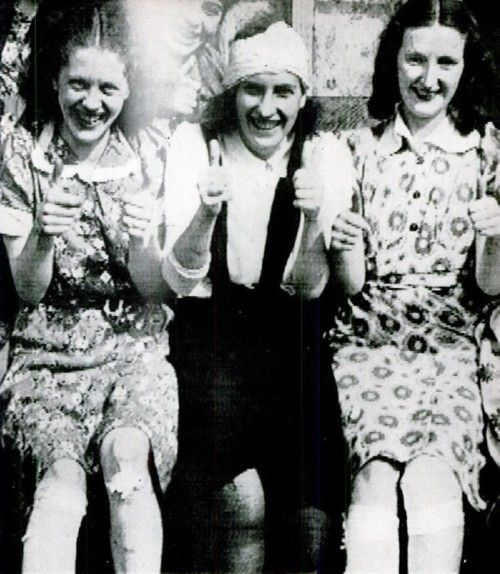 Three wounded , but optimistic british girls with thumbs up after August 15´s bombing in Croydon airport, London. 1940