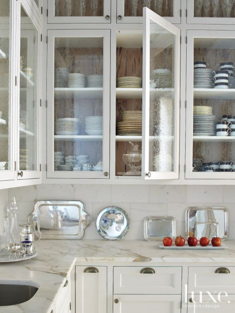 In the butler's pantry, Architectural Woodworks and Cabinetry created whiteframed bubble-glass doors for cabinets that are unusually backed in ancient pecky cypress. The backsplash, made of Calacatta gold marble from KeysGranite, was fabricated by Union Bay Investments.
