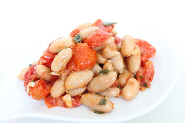 White bean and roasted tomato salad garnished with Grana Padano cheese and fried sage