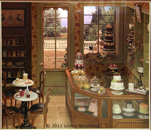 Using Strong Shapes to Accent Higher Views With the fantastic display of cakes, your eye tends to look mainly at the main pastry counter. Look at the ways the miniaturist pulls your eye upwards in this scene.
