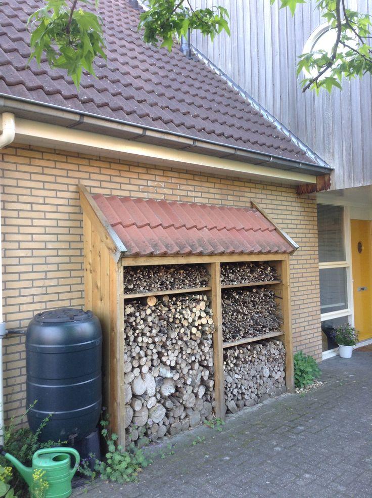 Zelfgemaakt hok voor open haard hout. De dakhelling van het dak en hok zijn gelijk, evenals de dakpannen.
