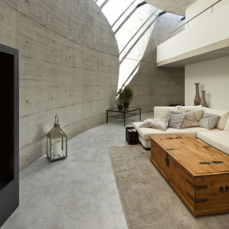 Immense curved concrete wall defines this minimalist living room, overlooked by a second floor catwalk in white. Natural wood chest coffee table is wrapped by a cream colored sectional at right.