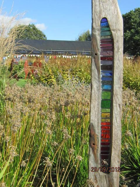 Garden art made from colored glass and drift wood | Sussex Prairies