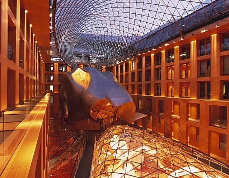"""""""The Berlin branch offices of the DZ Bank is one of the most interesting buildings from Frank O. Gehry. This 'typical Gehry trademark' is therefore located in the atrium: a glass, airship-like roof and expressive built-in features contrast with the strictness of the solid building structure.""""  read more at http://www.erco.com/projects/financial/dz-bank-berlin-branch-1232/en/intro-1.php"""
