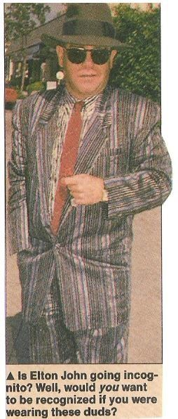 John, Elton / In Striped Suit, Red Tie, Black Hat | Magazine Photo with Caption (1987)