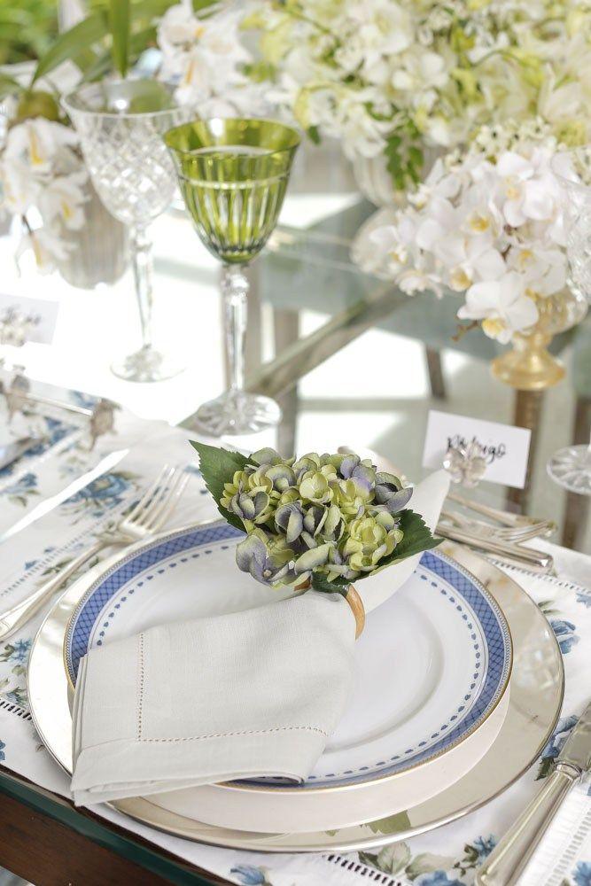 Para compor a mesa, louça Vista Alegre Cozinha daMatisse Casa,jogos americanosflorais azul e branco,porta-guardanapo de hortênsia verdeeguardanapos em linho verde oliva.