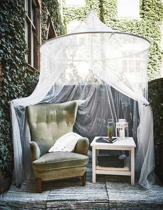A cozy corner is set up in a corner with an armchair, a side table and a canopy hanging above.