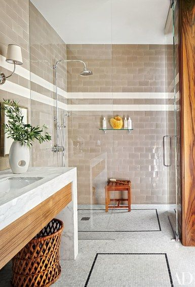 The shower fittings, shower shelf, teak stool, and mosaic-tile flooring in one guest bath in this Los Angeles home by Dan Fink are all by Waterworks | archdigest.com