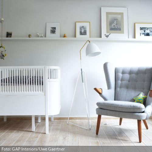 """Ein stylisches Möbel sowohl für das Baby als auch für den Behüter: Das Gitterbett """"Kili"""" von Sebra passt sich in der Größe dem wachsenden Kind an und sieht schön schlicht aus. Der graue Lounge-Sessel im Retro-Stil ist ebenfalls ein Hingucker."""