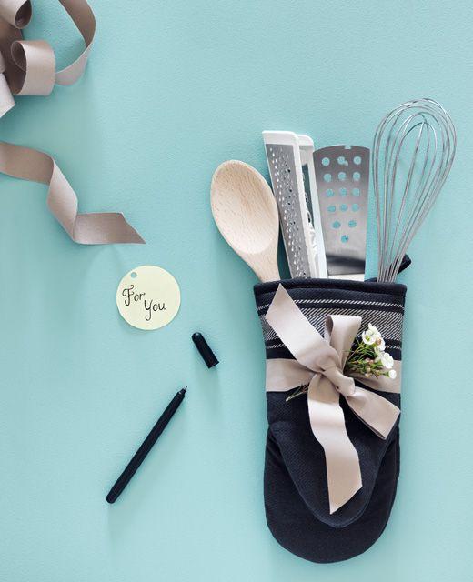 Chňapka naplnená kuchynskými potrebami previazaná stuhou. Stuha, pero a darčeková menovka vedľa nej.