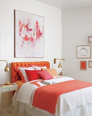 Love the orange w splash of pink, but also the low tufted headboard and low-hung art grouping.