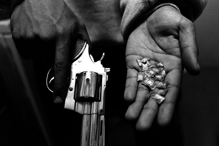 © Boogie (aka Vladimir Milivojevich), 2007, Brooklyn, NY - A gangster holds the tools of his trade: a gun and dime bags of crack cocaine, each with a street value of $5 USD / Summer Housing Public Housing Projects, Bedford Stuyvesant.