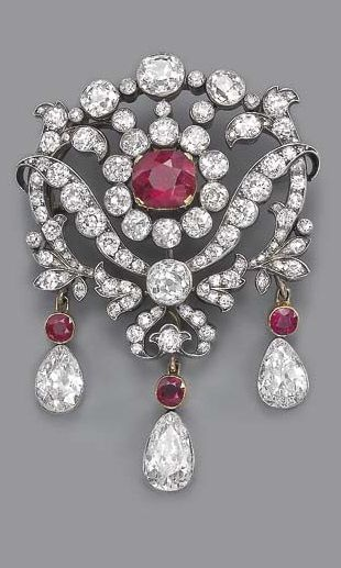AN ANTIQUE RUBY AND DIAMOND BROOCH. The central cushion-shaped ruby and old-cut diamond cluster to the openwork diamond floral surround, suspending three detachable pear-shaped diamond and ruby drops, mounted in silver and gold, circa 1880. #DiamondBrooches