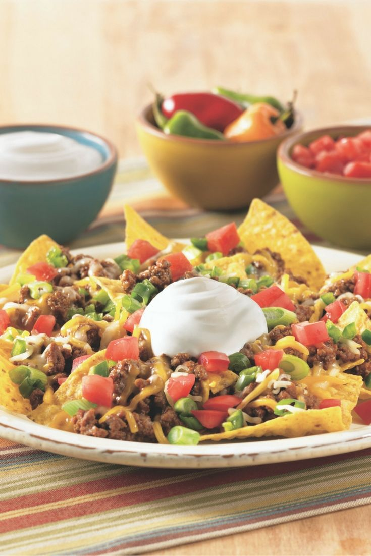 Layer ground beef, diced tomatoes, green onion, a sprinkling of cheddar cheese and a dollop of Daisy Sour Cream for the perfect nacho plate.