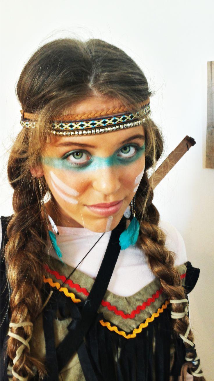 Maquillage fille indienne - foncez le teint avec une poudre bronzante - dessinez un trait de fard à paupières bleu turquoise qui passe en dessous des yeux et sur la paupière - dessinez 2 traits de fard à paupières blanc de chaque côté des jours et 1 en dessous de la lèvre - appliquez un rouge à lèvre clair - foncez légèrement les sourcils avec un fard à paupière marron