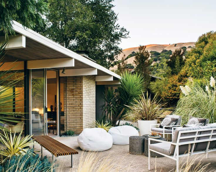 In the backyard of this Eichler home in San Rafael, California, a pair of white beanbag chairs, outdoor sofa, and chairs were sourced from West Elm and the Case Study Museum Bench is from Modernica. Photo by Drew Kelly.