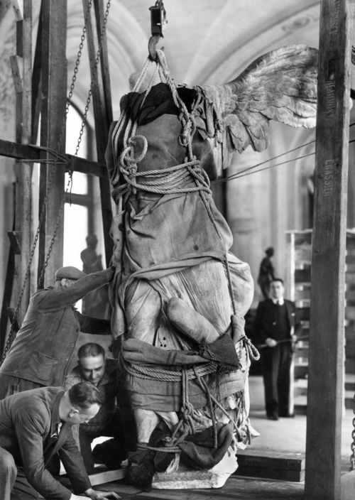 Showing workman boxing up statue for removal during WW11 part of Louvre exhibit    The Winged Victory of Samothrace  Source: livelymorgue