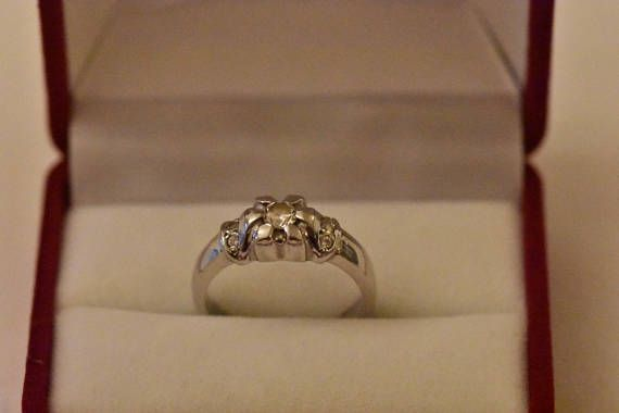 14kt white gold ring with flower motif . Set with 7 zircons