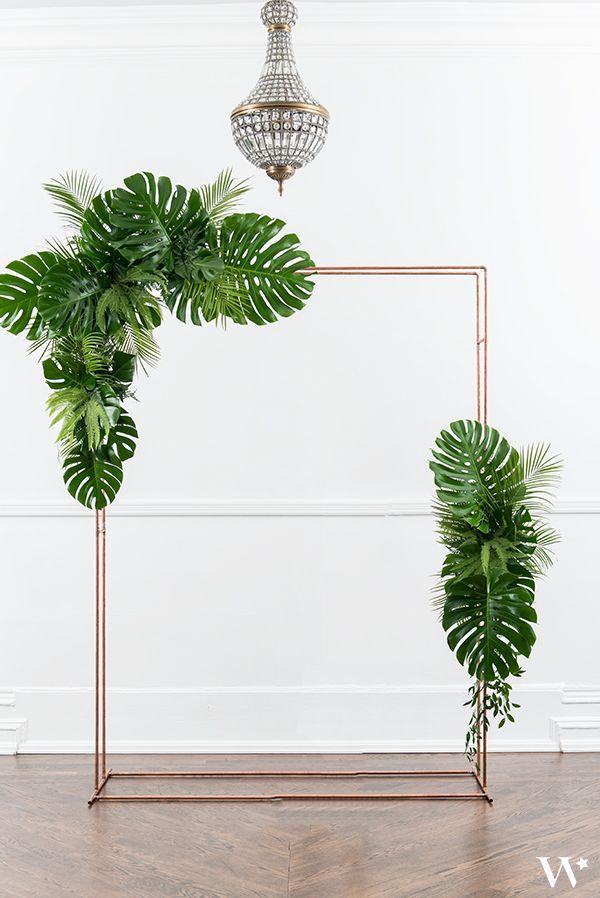 Tropische ceremonieboog met monsterabladeren en andere tropische palmbladen