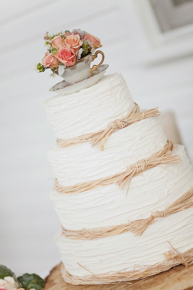 White four tiered cake with raffia and floral teacup topper.