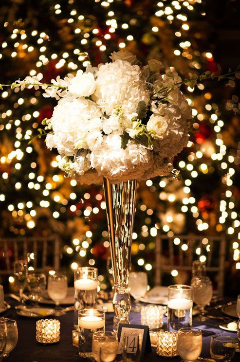 We love the classic elegance of this all white centerpiece offset by stunning candlelight. #WeddingCenterpieces