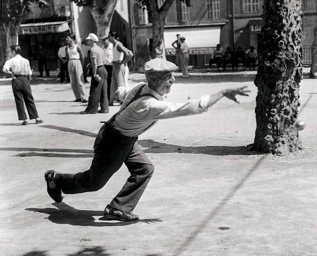 Willy Ronis, Partie de pétanque, Aubagne, 1947 I think this is a form of outdoor bowling. He's moving like a dancer to my eyes!