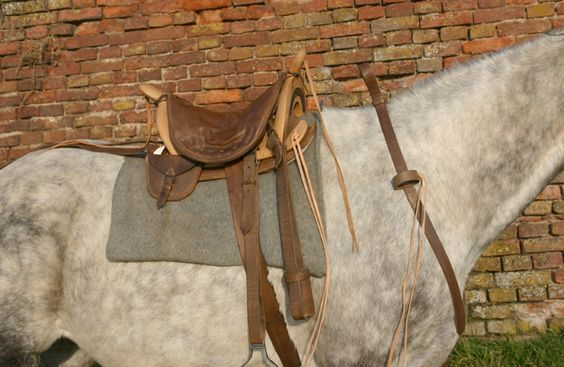 Trooper's saddle, early to mid 1800s, a bare wooden tree (frame) that sits on pads and a blanket, tie points at pommel and cantle, quilted leather seat.