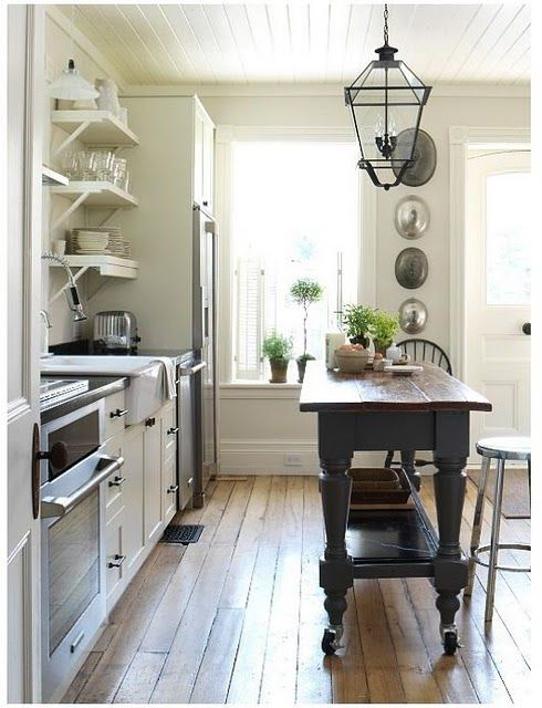 Love the island on wheels, the flooring, the ceiling, the simple trim, and the very little space this sweet kitchen takes.