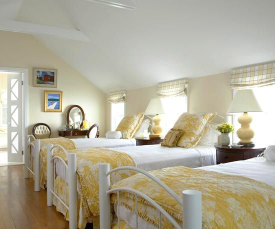 This enchanting dormitory-style bedroom features sunny-yellow quilted coverlets and matching bubble-shape lamps that pump up the play factor. White-painted trim, bedsteads, and linens offer a soft contrast to the creamy walls. Yellow-and-white checked fabric window shades bring in geometric pattern to coordinate with the toile coverlets./